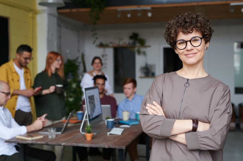woman wearing eyeglasses standing in front of meeting